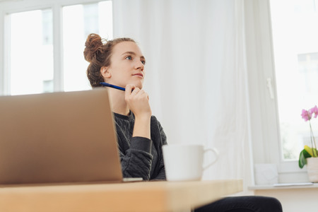 Thoughtful young woman working at a desk in an office sitting at her laptop looking up with a quiet contemplative expression