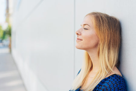 Young woman taking a moment to relax standing leaning against a white exterior wall with her eyes closed and a smile of pleasure Stock Photo