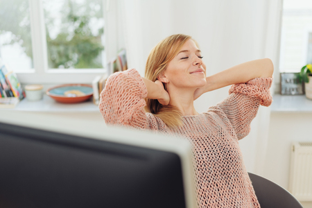 Young businesswoman stretching and relaxing sitting back in her chair with hands behind her head and closed eyes Stock Photo
