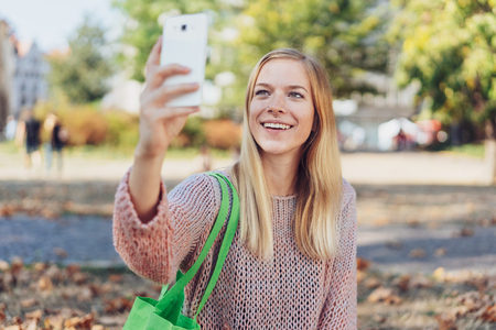 Young woman walking down a street in autumn taking a selfie with her mobile phone smiling as she poses for the camera