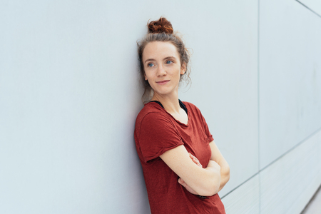 Thoughtful young woman leaning against a receding wall looking to the side with a smile and folded arms