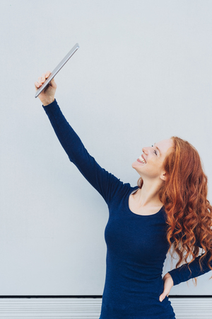 Happy young woman posing for a selfie on her tablet pc striking a pose against a white wall with a beaming smile