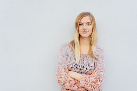 Confident pretty young blond woman standing with folded arms in front of a white wall with copy space