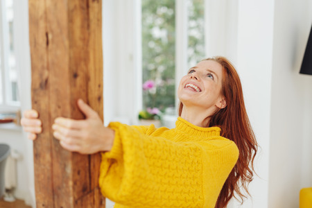 Joyful young woman celebrating at home holding onto a wooden post in her living room looking up with a happy smile