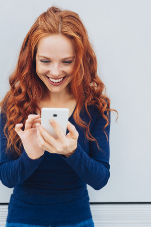 Portrait of young cheerful red-haired woman using mobile phone Stock Photo
