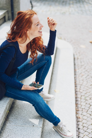 Portrait of young ginger smiling woman sitting on steps with mobile phone