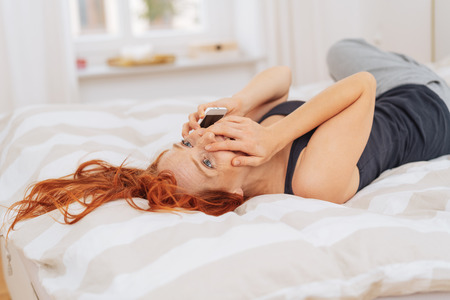 Surprised young woman lying on her bed in the morning chatting on a mobile phone with her hand to her mouth