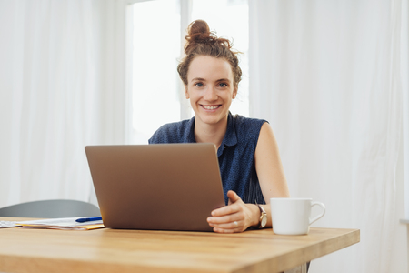 Happy young woman sitting studying at home on a laptop computer looking at camera with a friendly smile