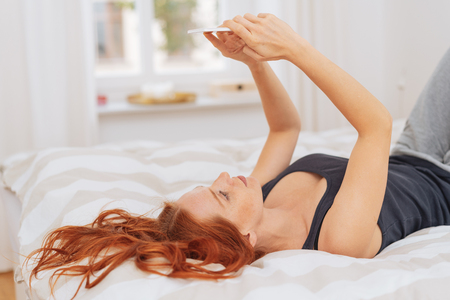 Young red-haired woman using mobile phone while lying on bed