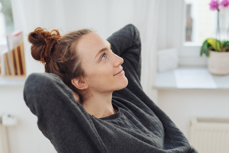 Attractive young woman sitting daydreaming with her hands behind her head and a pleased smile