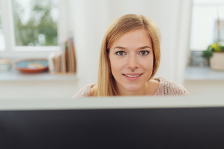 Intense young businesswoman staring at the camera over her top of her desktop monitor with a friendly smile Stock Photo