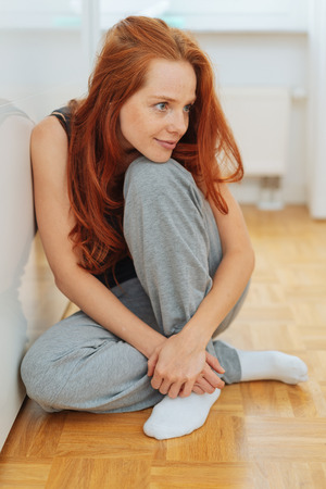 Attractive redhead woman sitting daydreaming on the wooden parquet floor in her home staring off to the side with a smile