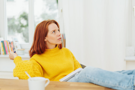 young woman sitting pondering a problem with her feet up on a wooden table as she stares up with a pensive expression