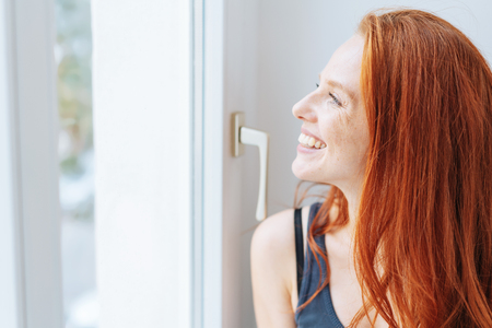 Smiling happy woman looking out of a window with the summer sunshine on her face in a health and wellness concept