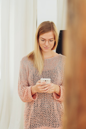 Smiling young woman dressed in pink knitted outfit looking down at smart phone while standing in front of curtain