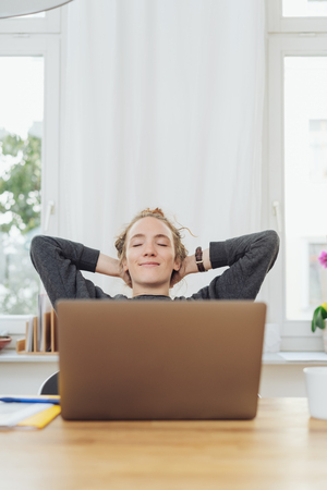 Pleased successful young businesswoman relaxing at work sitting back with her hands behind her head and a satisfied smile