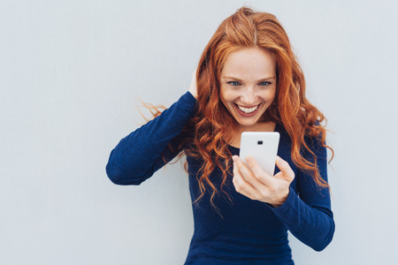 Woman wearing blue shirt scratching her neck while staring at white phone and standing in front of white background