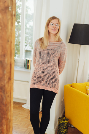 Adult woman wearing pink knitwear while leaning on white wall next to yellow armchair and black lamp