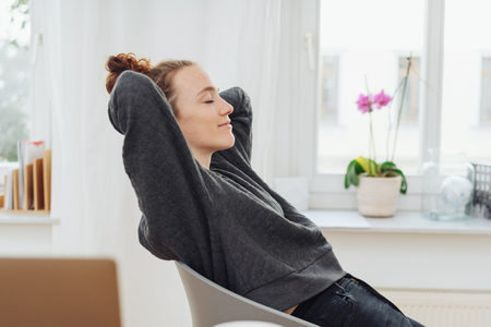 Young woman relaxing leaning back in her chair with her hands clasped behind her head and eyes closed