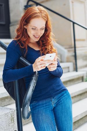 Linda mujer joven pelirroja de moda usando su teléfono móvil apoyado en una barandilla de hierro en pasos leyendo un mensaje de texto con una sonrisa