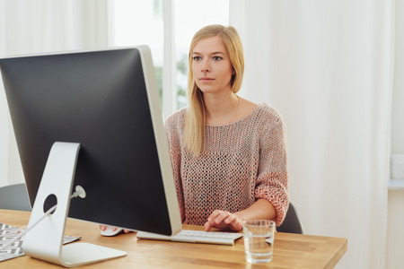 Portrait of young blonde woman working in front of computer monitor at desk