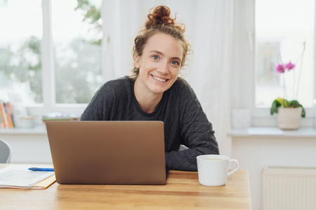 Happy young woman with a lovely warm smile seated at a wooden table with her laptop against a high key window background