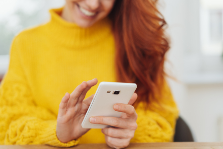 Lower face and body of your red haired woman in yellow sweater texting on mobile.