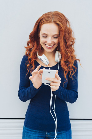 Pretty young redhead woman listening to music on a mobile phone standing selecting a new tune with a happy smile Stock Photo