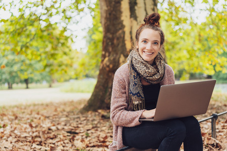 Smiling young woman sat in autumn park with laptop Stock Photo