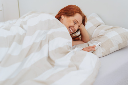 Smiling young red haired woman lying in bed with smartphone. Stock Photo