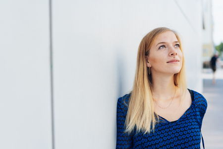 Young woman standing outdoors in an urban street daydreaming staring up into the air with a faraway expression Stock Photo