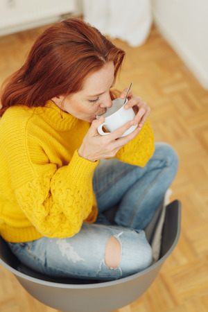 Woman with red hair relaxing squatting in a chair enjoying coffee cradling the cup in her hands viewed from above