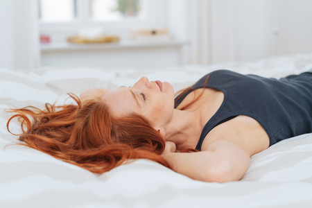 Young red-haired woman lying on bed with eyes closed Stock Photo