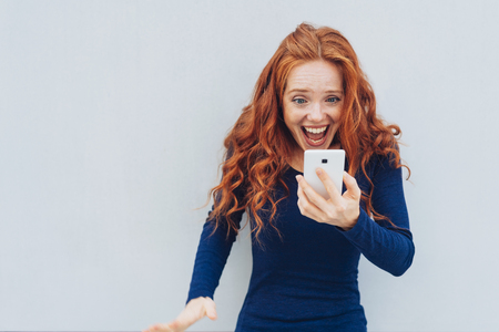 Adult female with red hair and blue long sleeved shirt exclaiming in awe at smart phone while standing in front of white wall Stock Photo