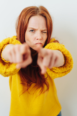 Angry young redhead woman pointing her fingers in blame with one eye closed in a wink and a serious focused expression