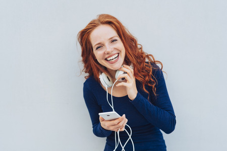 Happy adult woman with red hair and blue long sleeved shirt laughing while looking straight at camera Stock Photo