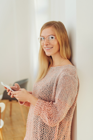 Friendly young blond woman wearing glasses standing leaning against a white wall holding her mobile and turning to smile at camera Stock Photo
