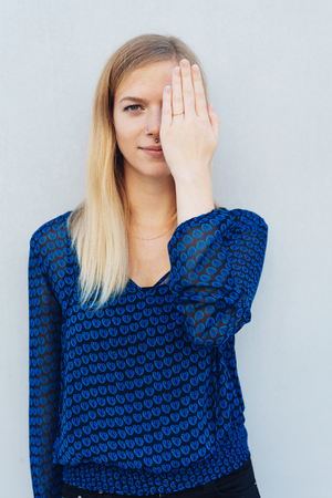 Young woman standing covering her eye with her hand as she looks at the camera with a smile Stock Photo
