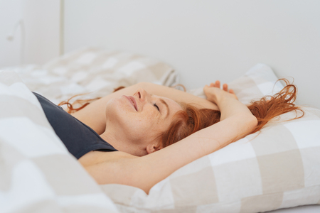 Side view of young pretty woman with red hair relaxing in comfortable bed Stock Photo