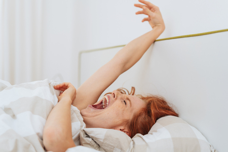 Portrait of young red-haired woman waking up in bed
