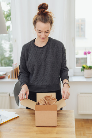 Young woman opening a brown cardboard box with a gift or order with a pleased smile of anticipation