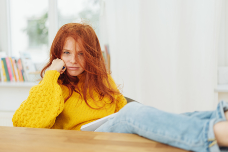 Disgruntled or confused young redhead woman with long tousled hair sitting with her feet up on the table glaring at the camera Stock Photo