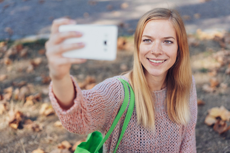 Smiling young woman taking a selfie on a mobile phone outdoors in autumn with a backdrop of dried fallen leaves