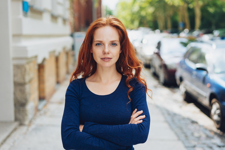 Thoughtful calm confident young woman standing with folded arms staring at the camera in an urban street