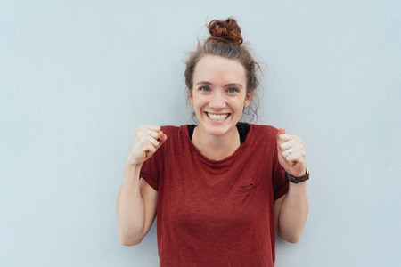 Excited young woman celebrating clenching her fists and looking at the camera with a beaming toothy grin against a white wall