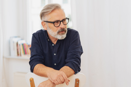Portrait of middle-aged bearded man with glasses sitting on chair