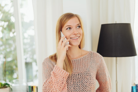 Young woman listening to a mobile phone call looking up with a delighted smile while standing in her living room