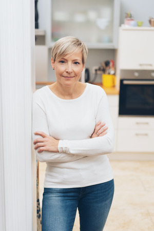 Attractive self-assured woman in her apartment standing with folded arms leaning against a wall looking at the camera