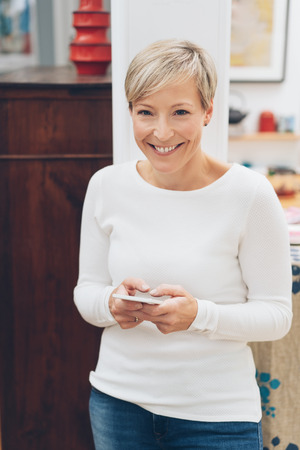 Vivacious middle-aged woman with a beaming smile standing indoors at home holding a mobile phone