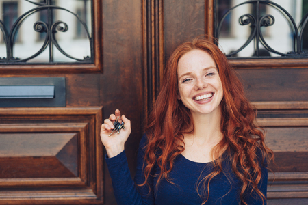 Grinning woman with red hair holding keys in closed hand while standing on front of wooden door in background